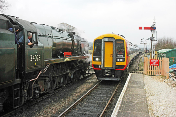 The train passes a Swanage Railway steam train at Harman's Cross