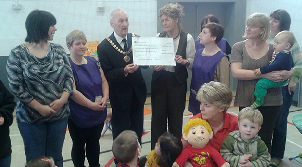 Ferndown Mayor Cllr Terry Cordery presents the cheque to Heatherlands Mum's & Tot's group leader Mary Melbourne and her team