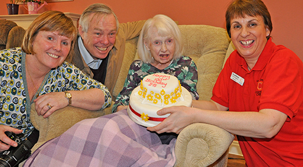 Iris Brain receives her 100th birthday cake from Fernhill's Activity Organiser Ann Marie Knight. Joining them are Iris's granddaughter Fiona Hammick and Fiona's father Merrick Williams, Iris's son-in-law.