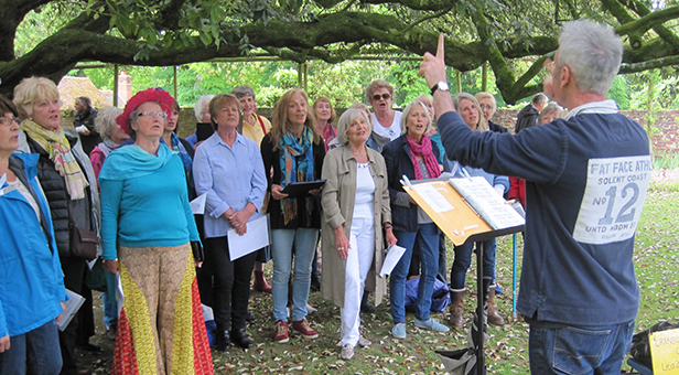 Standing under the ancient holm oak in the gardens of Cranborne Manor, the Cranborne Community Choir perform at the church fete