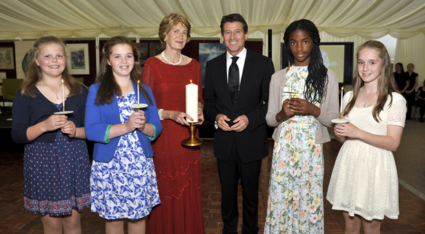 BANNER PHOTO: Lord Coe, Jane Nicholson (Sherborne Girls' new Legacy Leader) and Heads and Vice Head of junior boarding house West, from left, Sophie Wurfbain, Olivia Andrews, Melody Lulu-Briggs and Holly Stephens, participate in the candlelight ceremony at the Candlelight Ball to mark the relaunch of the legacy campaign with the new title 'Pass on the Light' and the launch of the School's new Candlelight Bursary Fund