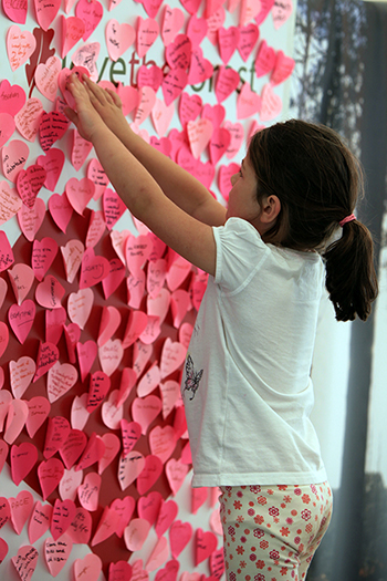 Girl sticks note to lovetheforest heart wall at the New Forest Show