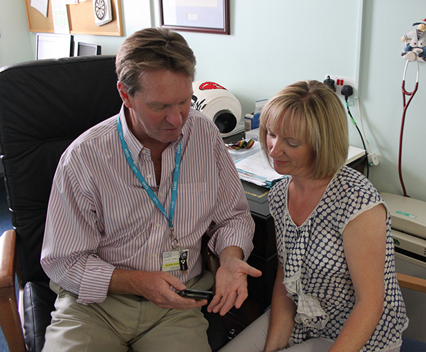 Professor David Kerr discusses some of the online care-management options with a colleague