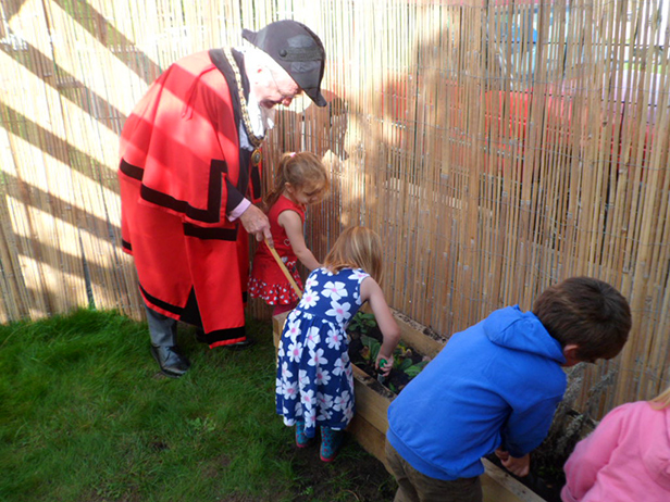 Mayor of Ferndown Cllr John Lewis planting flowers with kids at the Heatherlands Hopscotch Pre-school