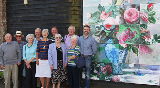 Artists gather next to the completed masterpiece outside Poundbury Gardens, taken by Neil Crick