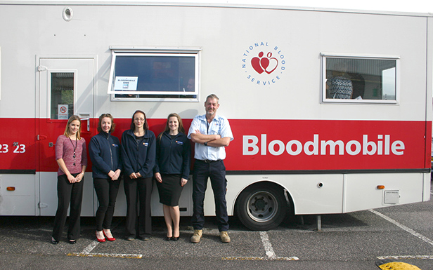 Staff at Hamworthy Heating in front of the bloodmobile