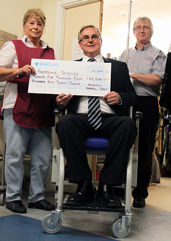 Dorinda Sheppard, Appeal Shop volunteer (left) and RBH Financial Accounts Manager Mike Wilkinson (centre – trying one of the new wheelchairs and finding it very comfortable) present Ian Barnett Potts, Porter Services Manager (right) with the new wheelchair funds