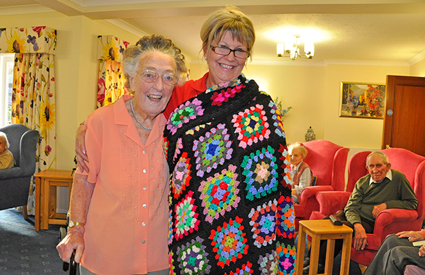 WRAPPED UP Brook View Activities Organiser Monique Brady models a crocheted blanket made in the home by resident Joan Murton, left