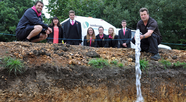 Lake into life: Stuart Paterson, Network Technician, Sembcorp Bournemouth Water (right) and James Short, Outdoor Education Leader, The Bourne Academy (left) together with SBW's Hazel Taylor and students watch as the lake is filled