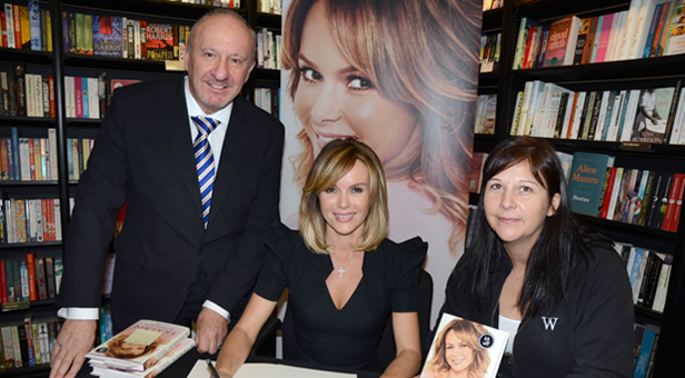 Amanda Holden signs the charity celebrity autograph book with Bill Riddle and Waterstone's senior book seller Michelle Lever.