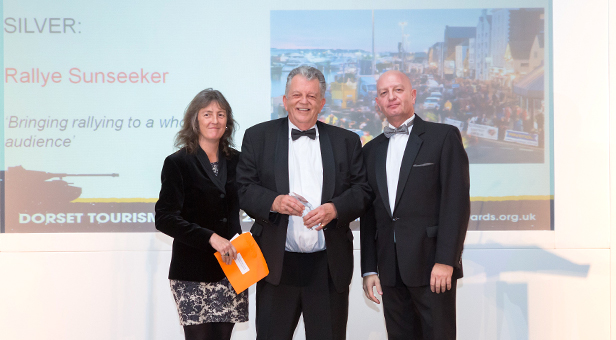 Adele Ladkin, Bournemouth University Department of Tourism presents Rallye Sunseeker Marketing Consultant Alex Mellon with the Silver Award, joined on stage by Master of Ceremonies Paul Kinvig