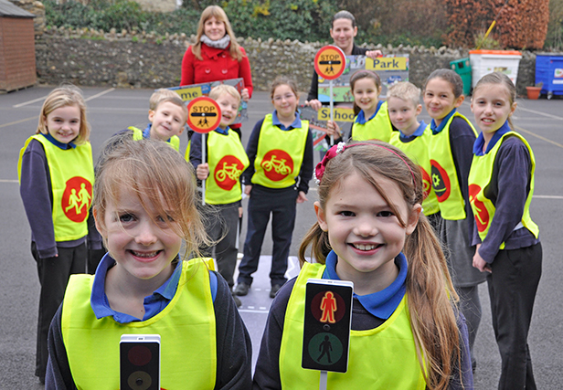 SAFETY FIRST. Year Two pupil Laura (left) and Year Three's Evie with fellow schoolmates at Sticklands Primary in Evershot. Joining them to try out the road safety kit are Battens personal injury solicitor Hannah Brown (rear left) and Sticklands headteacher Kathy McCann