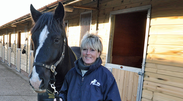 "Jane with ""Duke"" and the stables"