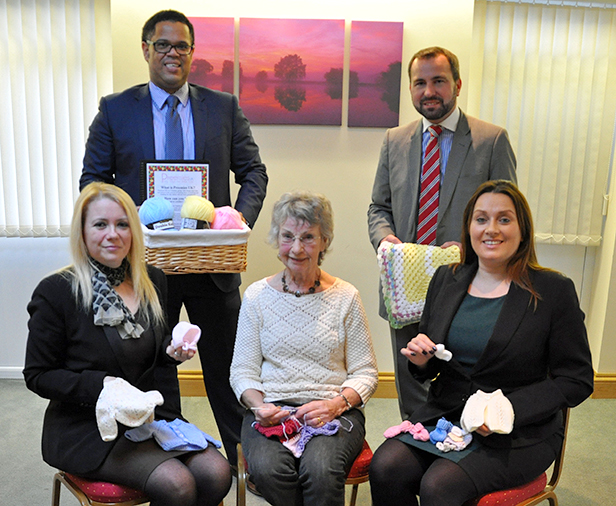 Nick Douch, (left) MD of Douch Family Funeral Directors and Shane Watson, Manager of the Ives & Shand branch. Front (l-r): Charlie Loveday, funeral director, Renee Guest, knitter, and Marcella McDonagh, funeral director