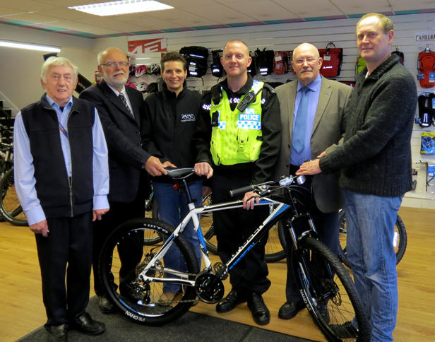 PC Avey-Hedditch picks up the bike watched by, from left, Brian Frecknall, chairman of St Leonards and St Ives Homewatch, Mike Dyer, chairman of St Leonards and St Ives Parish Council, Sharon Worsfold from Pedals, Rodger Long, chairman of West Moors Homewatch and Pete Holden, chairman of West Moors Parish Council.