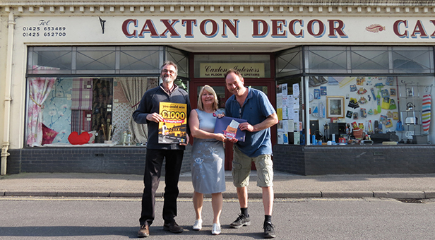 £1,000 FOR THE COMMUNITY L-R Steve Moody, Caxton Décor with Janine Pulford, Director mags4dorset and winner Mike Womersley receiving his cheque