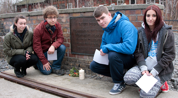 Students from The Arnewood School (from right to left) Jasmine Goodman, Calum Thompson, Simon Bennison and Steph Peacock with the candle lit in memory of the Berlin Jews deported from Grunewald Station.