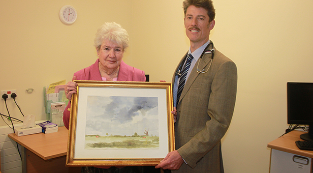 Patient Mary Smallman hands over her painting to Dr Owen David