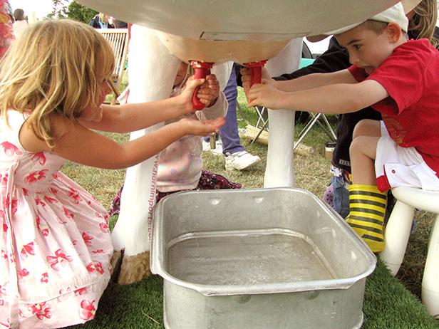 Children milking Camilla the cow from Dike & Son at Stock Gaylard Oak Fair