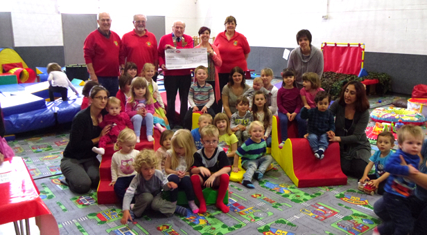 Children already on the new pieces with Lisa Guy receiving the cheque from the Lions in the background