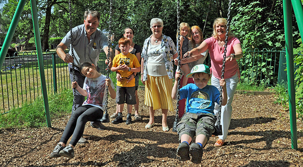 Trelawney Dampney, Eco's Managing Director (left) and Cllr Margaret Phipps (right) demonstrate the new swings watched by Yvette Greatrex, Vice Chairman, Hurn Parish Council, and parents and children