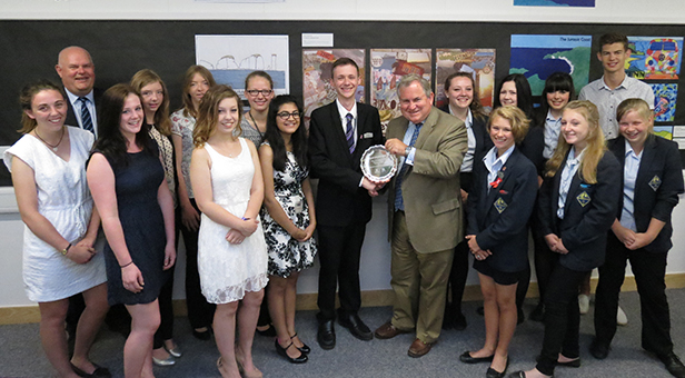 Bob Walter presents the award to Joe McMullen and the school council watched by Martin McLeman