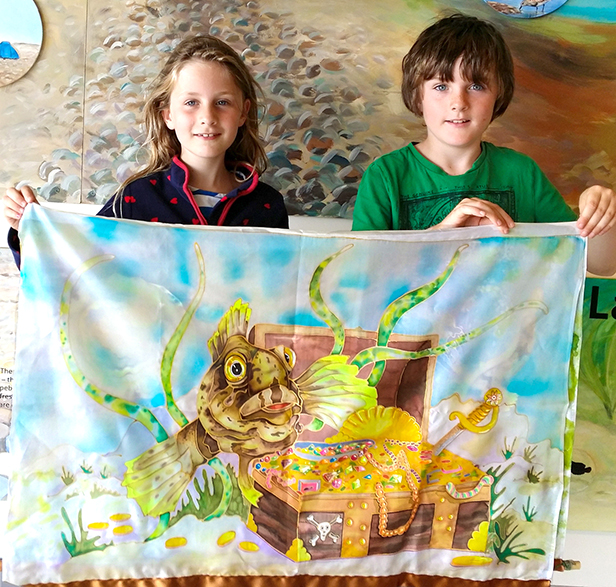 Children holding a painting of Bizzy the Blenny at the Chesil Centre