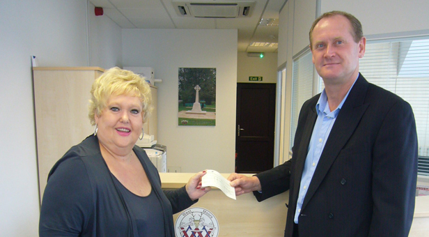 Pete Holden, chairman of the parish council, handing over the grant cheque to Mrs Ann Pogson, chairman of the memorial hall.