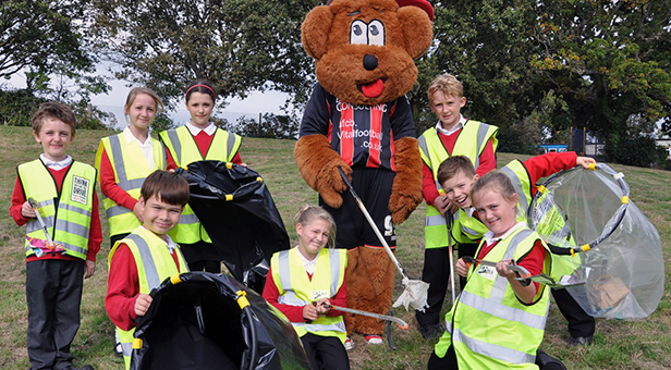 AFC Bournemouth mascot Cherry Bear helping Elm Academy children during a litter pick of a park in West Howe