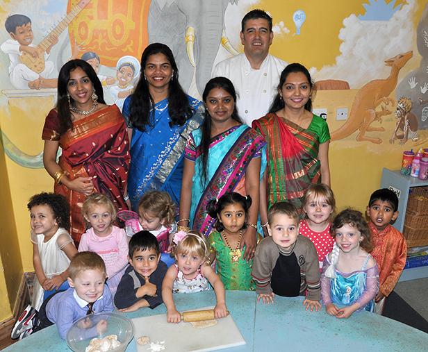 Chef Andy Daysh, nursery nurse Yogita Kapoor parents Viji Arunsankar and Moorthima Mohanraj and nursery nurse Dhara Jadeja, watch as children make chapattis as part of the Diwali celebrations