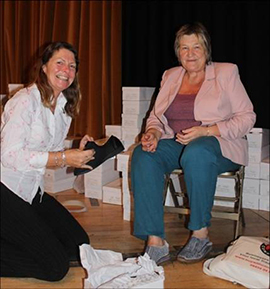 Sue Warr from POPP gives a pair of slippers to a visitor
