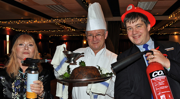 READY TO IGNITE: (left to right) Toyah Willcox puts a flame to the pudding held by head chef Tony Shepard, while guest services manager Andy Thompson holds the fire extinguisher at the ready