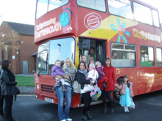 Parents and toddlers standing in front of panto bus