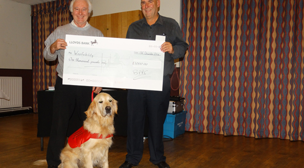 Andy (left) receives the cheque from BPPC chairman Gary Baker with Bubba in foreground