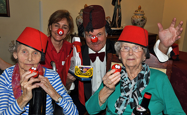 Tommy Cooper impersonator Clive Greenaway marks Comic Relief with Canford Chase Activities Organiser Maria Grant and residents Jean Palmer and Sylvia Sansome