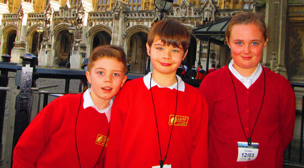 Three Elm Academy children stand in front of the Houses of Parliament, from left to right: Brendan Waters, Robert Stanners and Madison Croft Parliament.