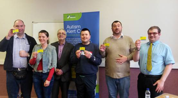 Members of Bournemouth Drop In Group receive the first Autism Alert Cards for Bournemouth, Dorset & Poole from Bob Lowndes, Chief Executive of Autism Wessex