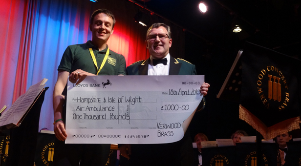 Philip Reeves of the Hampshire & Isle of Wight Air Ambulance Service receiving a donation of £1,000 from Verwood Concert Brass band member Robin Lock.
