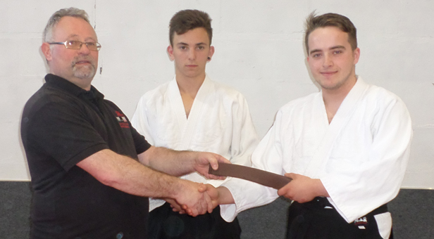 Hatamoto Sensei John Hanrahan handing Sensei Jordan Lee his 1st Kyu adult brown belt at Ferndown Jitsu Club