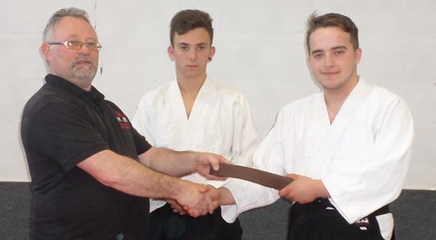 Hatamoto Sensei John Hanrahan handing Sensei Jordan Lee his 1st Kyu adult brown belt at Ferndown Jitsu Club