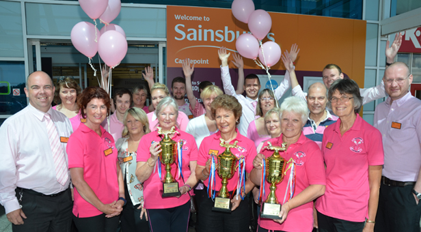 (from left) Paul Barlow and Sainsburys staff, with members of Bournemouth's Pink Champagne Dragon Boat Team.