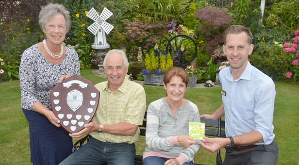 Winners Barrie and Shelia Smith receive the Ferndown In Bloom shield from Jean Read (left) and gift card from Matt Hill (far right)