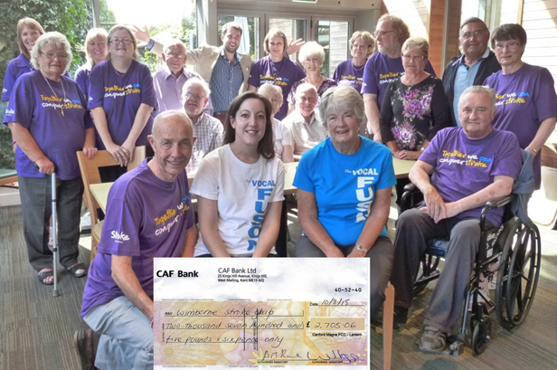 Cheque presentation by Lynne Turner of Vocal Fusion with Timothy Medhurst from Dukes of Dorchester 'celebrating' in the background.