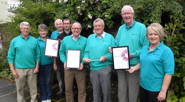 Some members of the Wimborne in Bloom Committee with their awards and Glen Holdsworth, the Town Council groundsman (wearing a black top) responsible for maintaining Redcotts Recreation Ground