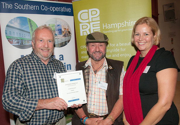 Pondhead Conservation Trust volunteers Derek Tippetts and Dave Dibden are presented with their Community and Voluntary award, presented by Gemma Lacey from The Southern Co-operative