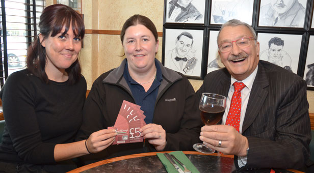 (From left) Natalie Doody presents vouchers winner Carly Reeves with Peter Matthews