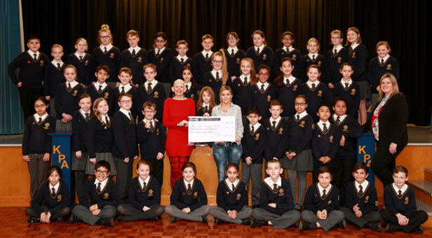 A SCHOOL EFFORT - Year six pupils celebrate Molly's Hair Raising Event - with Sue Hampton (middle in red), Molly Milligan (to her left) and Molly's mum Claire Heaton (holding cheque). Associate principal Dawn Wilks is far right