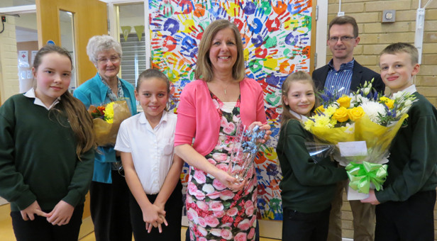 Schools out for Mrs Gould (centre) with gifts of an engraved vase from the school, flowers held by Brendon and Sienna, a photo canvas held by her husband Quartus and her mother Mary Woods, featuring the hand prints of all of the school's 187 children including Alissa (far left) and Mia (left).
