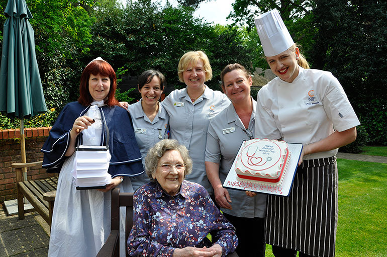 Chef Lorna Parsons presents the Nurses' Day cake in the garden at Colten Care's Amberwood House in Ferndown