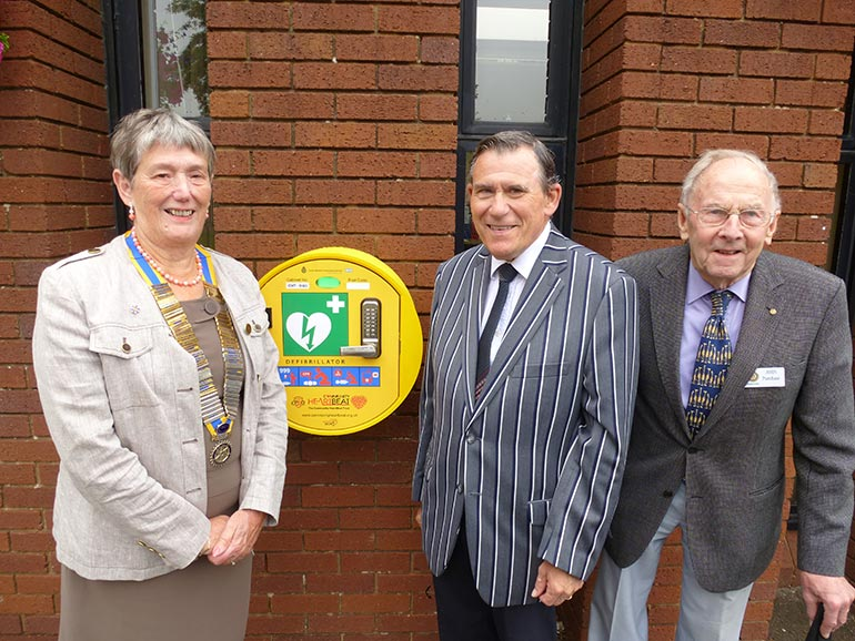 Sue Young (L), President of Wimborne Rotary by the new defibrillator with Councillor David Morgan and Rotarian John Purchase (R)